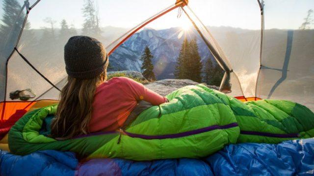 saco de dormir mulher sol montanhas